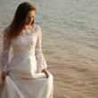 Bride in lace dress is standing near waterline — Stock Photo