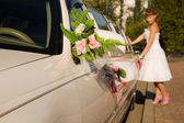 Bride is standing by limousine car — Stockfoto