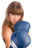 Active young female in blue boxing gloves — Stock Photo
