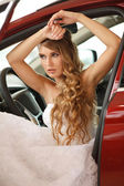 Young bride sits in car — Stock Photo