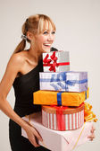 Cheerful young woman with heap of gifts — Stock Photo