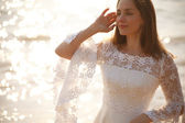 Bride in lace dress near sparkling water — Stock Photo