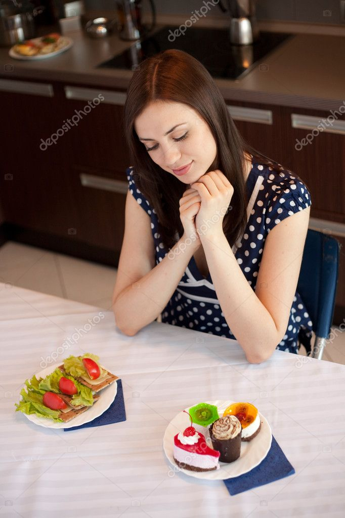 Young woman at her kitchen and choosing between diet sandwiches and fancy cakes — Stock Photo #14176392