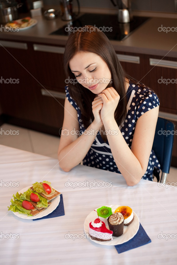Young woman at her kitchen and choosing between diet sandwiches and fancy cakes — Foto de Stock   #14176392