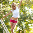 Young woman on ladder — Stock Photo