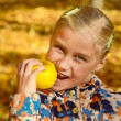 Little smiling girl eating apple in the park with bright autumn — Stock Photo