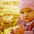 Little lovely girl holding an apple with bright autumn leaves on — Stock Photo