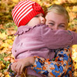 Two little girls embracing one another in the autumn park — Stock Photo