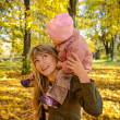 Young woman walking with her little child in the bright autumn — Stock Photo