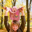 Young woman playing with her little child in the bright autumn — Stock Photo
