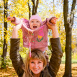 Young woman playing with her little child in the bright autumn — Stock Photo #14365219