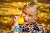 Peu souriant girl eating apple dans le parc avec automne lumineux — Photo
