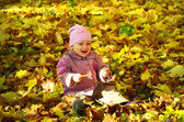 Little lovely girl sitting on maple leaves in the park and laugh — Stock Photo