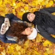 Young couple relaxing on autumn leaves — Stock Photo