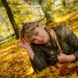 Young woman relaxing in the bright autumn park — Stok fotoğraf