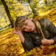 Young woman relaxing in the bright autumn park — ストック写真