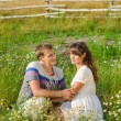 Young loving couple embracing each other sitting in grass — Stock Photo #38285275