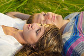 Close up photo of a loving young couple lying in the grass — Stock Photo