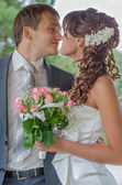 Happy young bride and groom embrace and kiss — Stock Photo