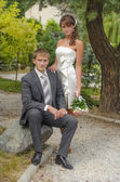 Bride and her groom sitting on a stone — Stock Photo