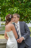 Young wedding couple standing over green tree background — ストック写真