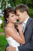Young wedding couple standing over green tree background — Stock Photo