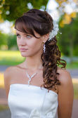 Beautiful bride closeup portrait over green trees outdoor — Stock Photo
