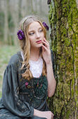 Beautiful young girl sitting near a tree — Stock fotografie