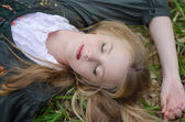 Close up portrait of a girl sleeping on the grass — Stock Photo