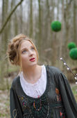Pensive pretty girl  with decorative green balls on background — Stock Photo