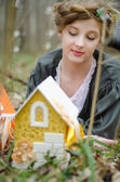 Younh girl looking at vintage doll house — Stock Photo