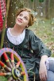 Girl posing near vintage wheel — Stock Photo