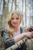 Picture of beautiful girl touching birch branches and smiling — Stock Photo