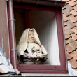 Stock Photo: Statue of a nun in a window on the roof. Brugge Belgium