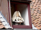 Statue of a nun in a window on the roof. Brugge Belgium — Stock Photo
