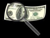 Hundred dollar bill and magnifying glass isolated on black — Stock Photo