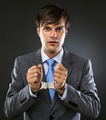 Young caucasian businessman with handcuffed hands — Stock Photo