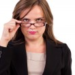 Businesswoman looking over glasses — Stock Photo #14030556