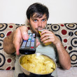 Young man watching television, eating potato chips and drinking  — Stock Photo