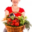 Happy young woman showing a basket with fresh vegetables — Stock Photo #27276157