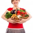 Happy young woman holding basket with vegetables — Stock Photo
