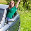 Happy young woman waving out the window — Stock Photo #27276187