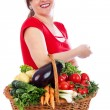 Happy young woman holding basket with fresh vegetables — Stock Photo