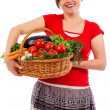 Happy young woman holding basket with vegetables — Stock Photo #27276227