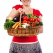 Happy young woman holding basket with fresh vegetables — Stock Photo #27276313