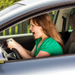 Young woman screaming while driving the car — Stock Photo