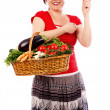 Happy young woman holding a basket with fresh vegetables and sh — Stock Photo #27276327