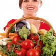 Happy young woman showing a basket with fresh vegetables — Stock Photo