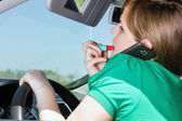 Young woman driving , applying lipstick and speaking on her smar — Stock Photo