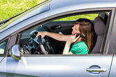 Young woman with hand on steering wheel using mobile phone — Stock Photo